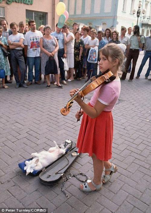 Девочка играет на скрипке перед толпой, а ее собака развалилась в футляре для скрипки на улице Арбат в Москве.