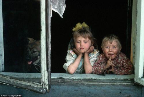 Двое грязных детишек выглядывают из окна в горно-металлургическом городке в Сибири.