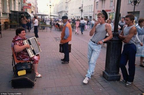 Женщина играет на аккордеоне на популярной пешеходной улице Арбат в Москве, а несколько стоящих мужчин ее слушают.