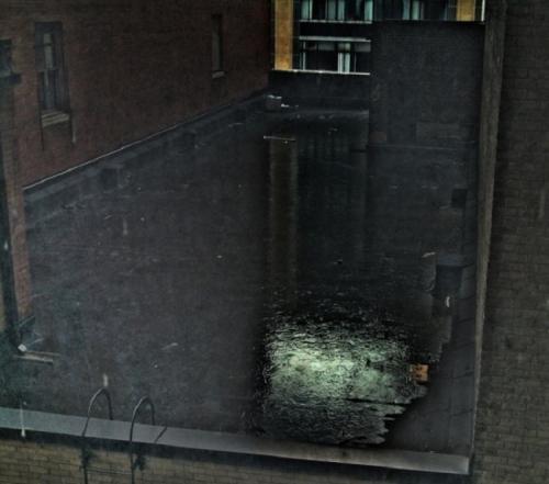 Лужа на крыше в тихом дворике сразу после дождя.